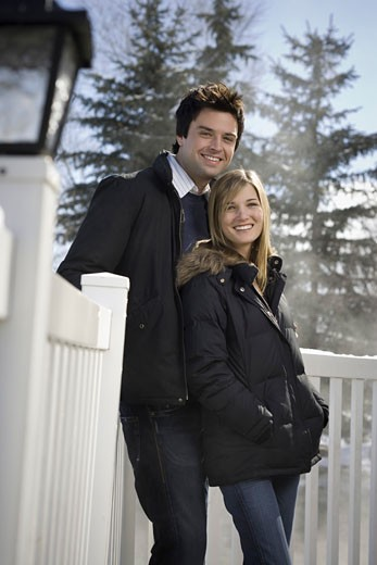 Stock Photo: 1660R-8758 Portrait of a young couple standing beside a fence