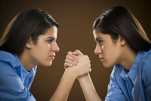Stock Photo: 1660R-8817 Profile of two teenage girls arm wrestling