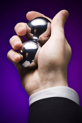 Close-up of a businessman's hand holding two metal balls : Stock Photo