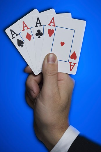 Close-up of a person's hand holding four aces : Stock Photo