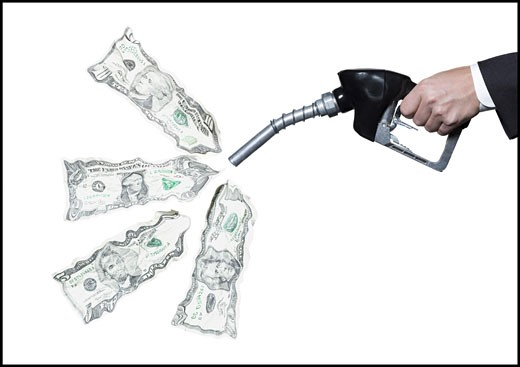Close-up of a person's hand holding a fuel pump with dollar bills coming out of it : Stock Photo