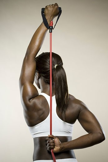 Stock Photo: 1660R-8934 Rear view of a young woman exercising with a jump rope