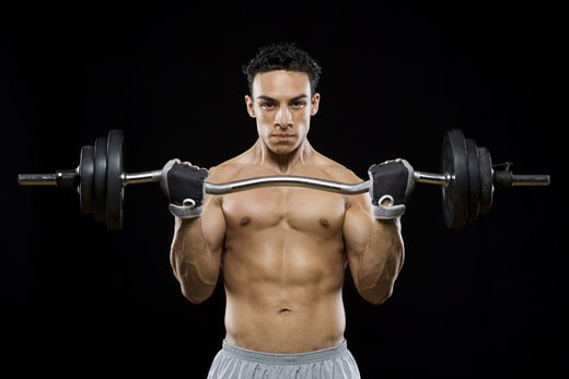 Portrait of a mid adult man lifting a barbell : Stock Photo