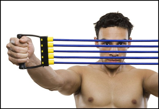Portrait of a mid adult man stretching a resistance band : Stock Photo