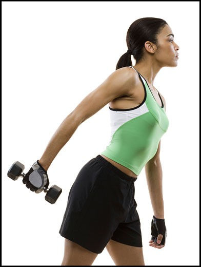 Stock Photo: 1660R-8952 Profile of a young woman exercising with a dumbbell