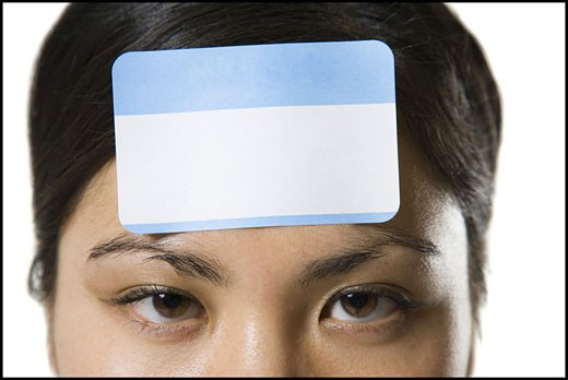 Portrait of a young woman with a blank name tag on her forehead : Stock Photo