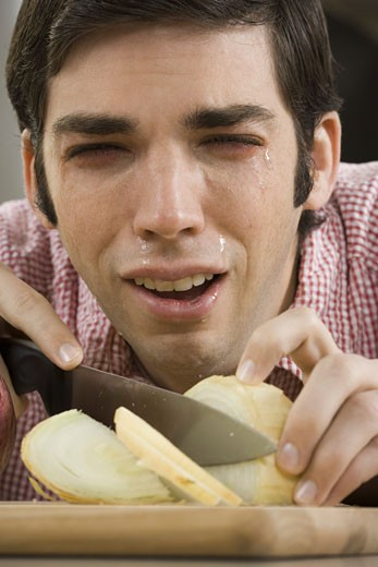 Close-up of a young man with tears in his eyes while cutting onions : Stock Photo