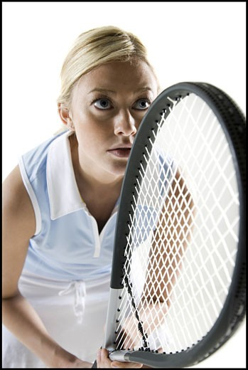 Close-up of a young woman holding a tennis racket : Stock Photo