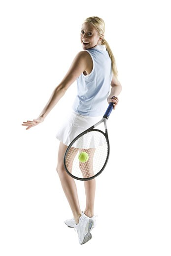 Rear view of a young woman playing tennis : Stock Photo