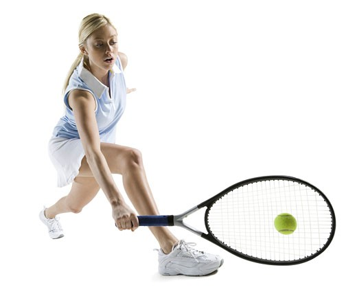 Young woman hitting a tennis ball : Stock Photo