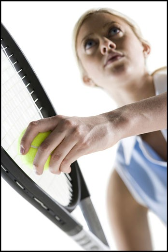 Stock Photo: 1660R-9140 Low angle view of a young woman playing tennis