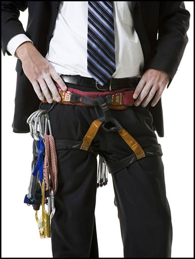 Mid section view of a young man wearing a harness around his waist : Stock Photo