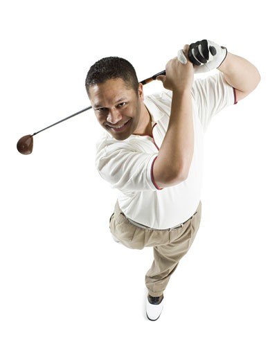 High angle view of a mid adult man swinging a golf club : Stock Photo
