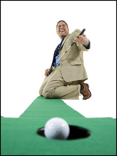 Stock Photo: 1660R-9176 Businessman playing golf on artificial turf