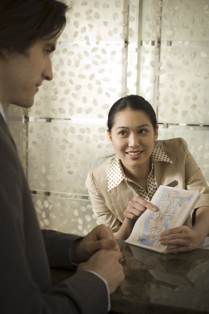 Stock Photo: 1660R-9302 Businesswoman showing a map to a businessman