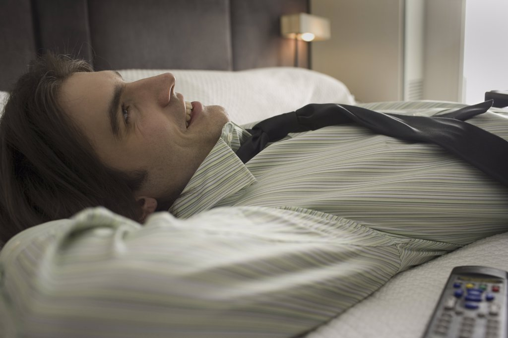 Stock Photo: 1660R-9319 Close-up of a businessman lying on the bed