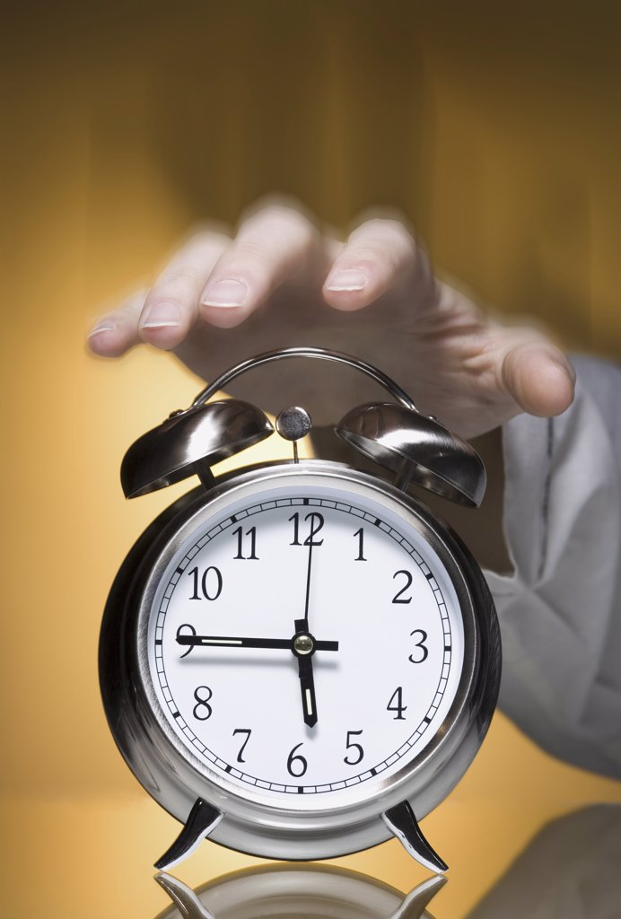 Stock Photo: 1660R-9364 Close-up of a person's hand reaching out for an alarm clock
