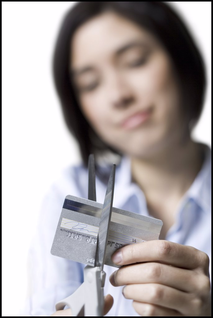 Close-up of a young woman cutting a credit card with a pair of scissors : Stock Photo