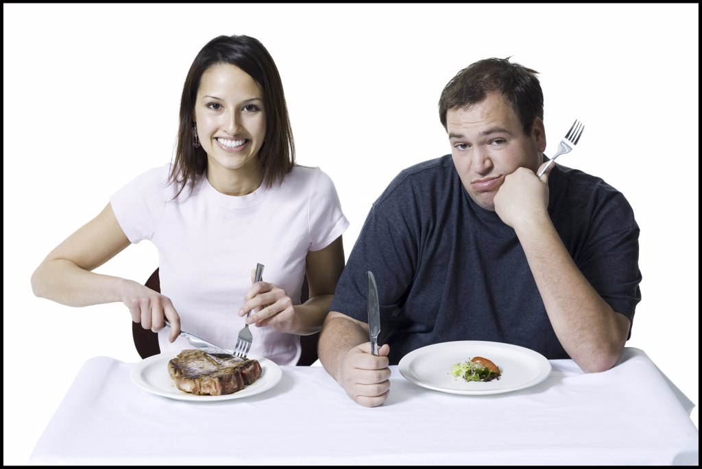 Portrait of a young couple sitting at the table : Stock Photo