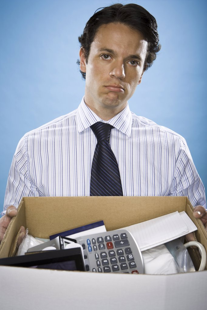 Portrait of a businessman holding a cardboard box full of belongings : Stock Photo