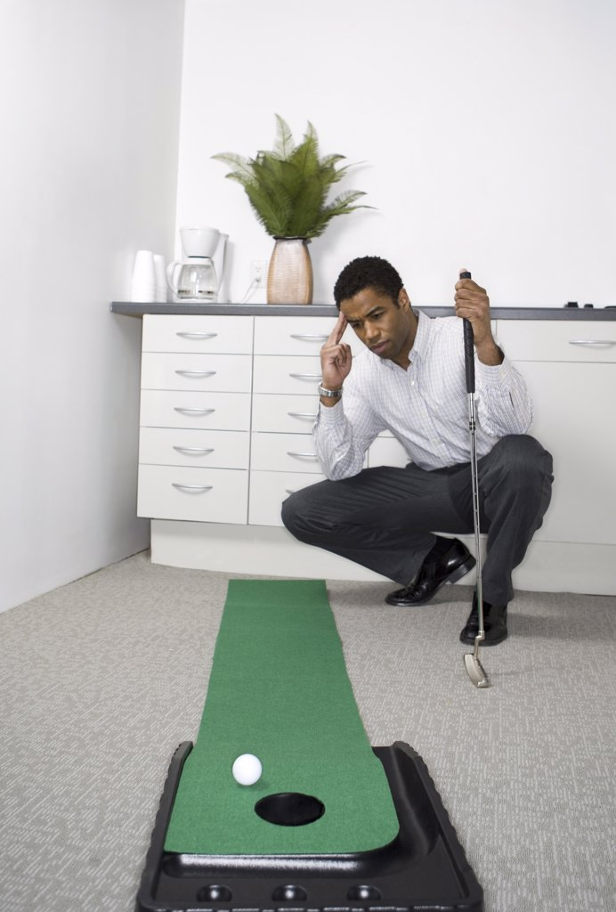 Stock Photo: 1660R-9925 Mid adult man practicing golf in the office