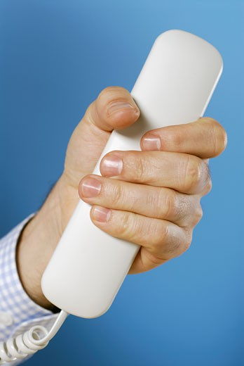 Close-up of a person's hand holding a telephone receiver : Stock Photo