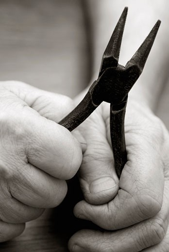 Close-up of a person's hands holding a pair of pliers : Stock Photo