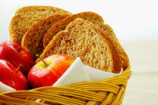 Close-up of apples and brown bread in a basket : Stock Photo