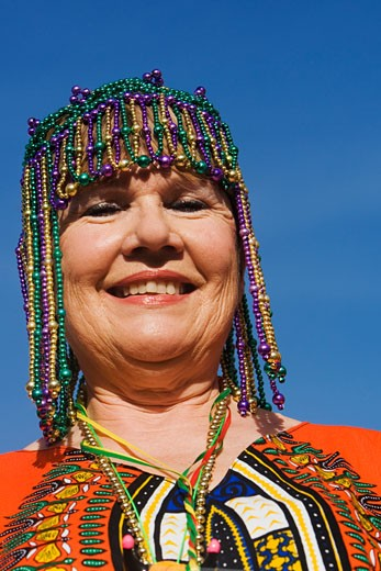Portrait of a senior woman wearing a beaded headdress and smiling : Stock Photo