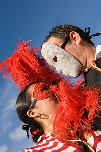 Low angle view of a man and woman wearing masks and looking at each other : Stock Photo