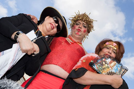 Low angle view of a mature man with two mature women wearing costumes : Stock Photo