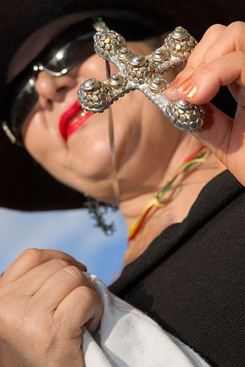 Stock Photo: 1663R-15186 Low angle view of a mature woman holding a cross