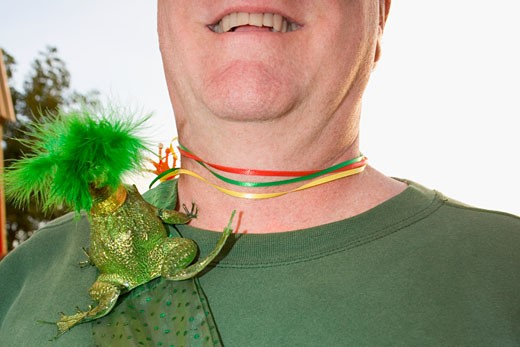 Close-up of a toy frog on a man's shoulder : Stock Photo