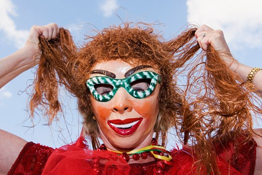 Low angle view of a woman wearing a carnival mask and holding her hair : Stock Photo