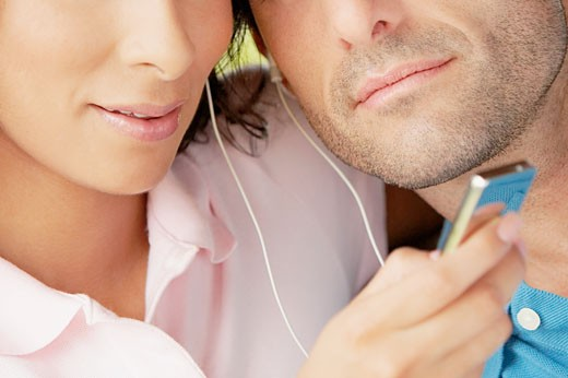 Stock Photo: 1663R-15447 Mid section view of a mid adult couple listening an MP3 player