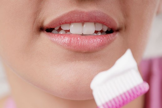 Stock Photo: 1663R-15540 Close-up of a young woman with a toothbrush in front of her mouth