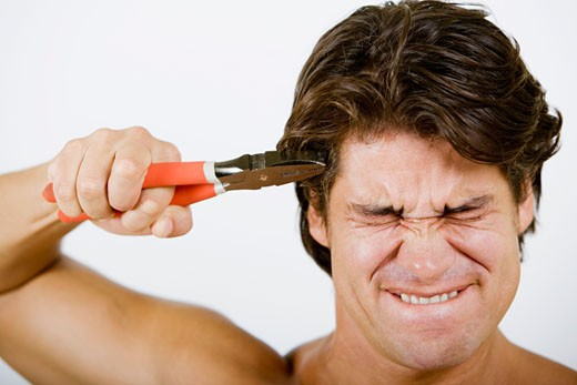 Stock Photo: 1663R-15792 Close-up of a mid adult man pressing pliers up to his head