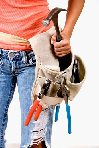 Mid section view of a person holding a hammer in a tool belt : Stock Photo