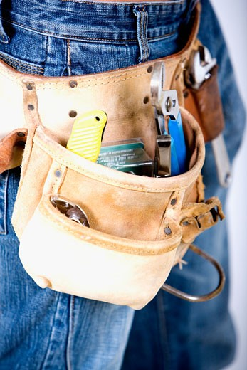 Mid section view of a man wearing a tool belt : Stock Photo