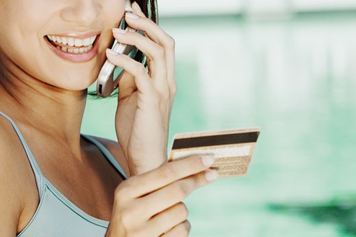 Stock Photo: 1663R-15990 Close-up of a young woman holding a credit card and talking on a mobile phone