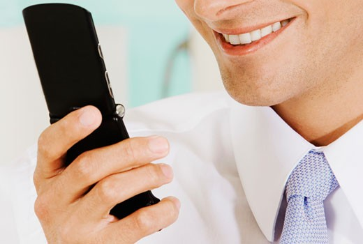 Stock Photo: 1663R-16069 Close-up of a businessman holding a mobile phone and smiling