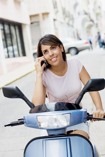 Stock Photo: 1663R-16413 Teenage girl riding on a motor scooter and talking on mobile phone