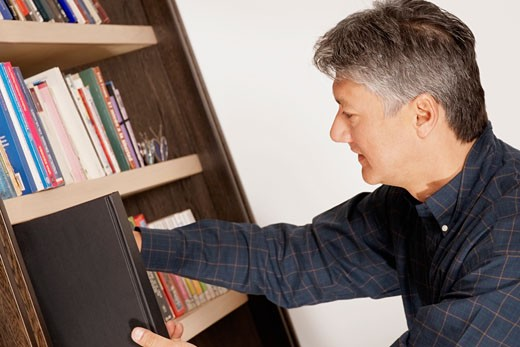 Side profile of a senior man picking a book from a bookshelf : Stock Photo