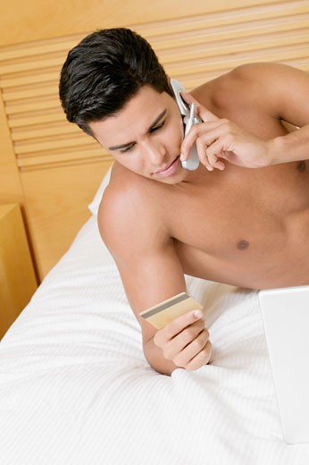 Young man talking on a mobile phone and holding a credit card : Stock Photo