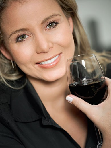 Portrait of a mid adult woman holding a glass of red wine : Stock Photo