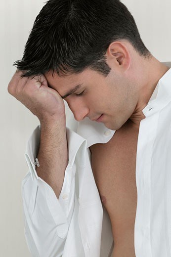 Close-up of a young man thinking with his hand on his forehead : Stock Photo