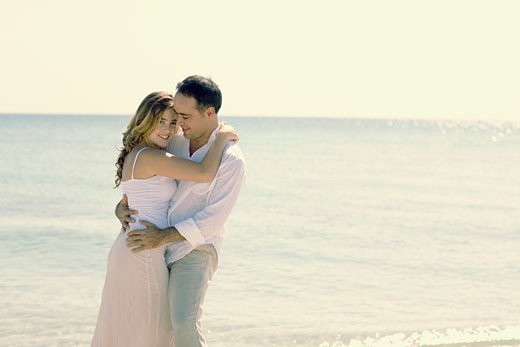 Stock Photo: 1663R-16983 Side profile of a young woman and a mid adult man embracing each other on the beach