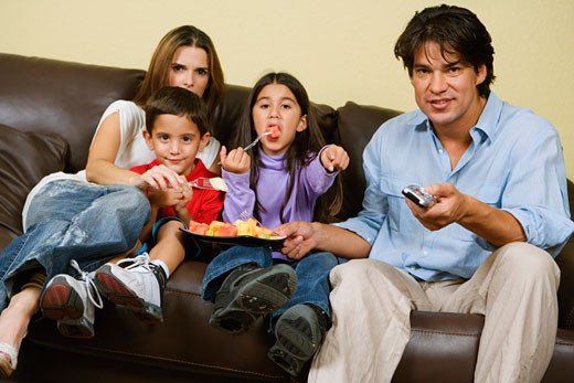Stock Photo: 1663R-17007 Mid adult couple with their children sitting on a couch and watching television