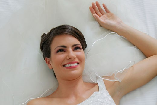 High angle view of a bride lying on the bed and smiling : Stock Photo