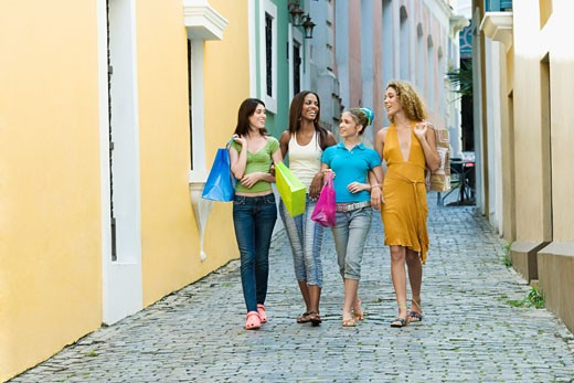 Four teenage girls walking in an alley and holding shopping bags : Stock Photo